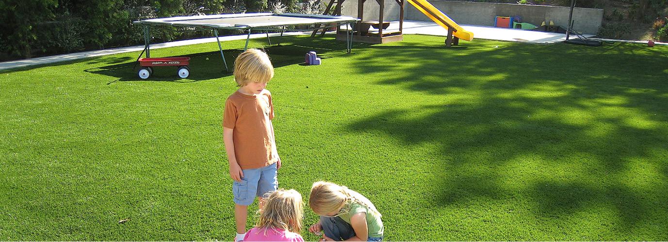 Kunstgras aangelegd in tuin met spelende kinderen
